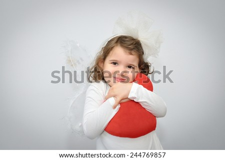 Cute young girl with a wings of fairy and alice band with a white bow holding a plush red heart on Valentines day - stock photo