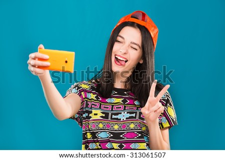 Cute young girl, with dark straight hair, wearing in colorful blouse and orange cap, makes selfie on her smart phone on blue background, waist up - stock photo