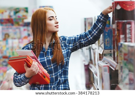 Cute young girl with long brown hair wearing blue plaid shirt shopping at book store, holding books and touching shelf, copy space. - stock photo