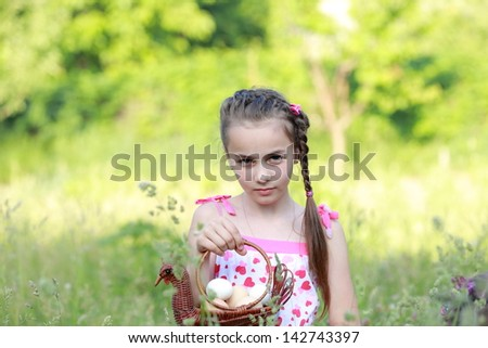 Cute young girls are on the green grass in the forest and keeps a beautiful basket with eggs - stock photo