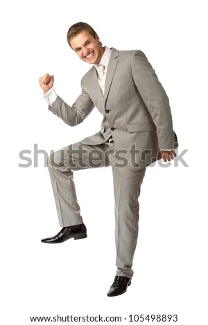 Cute young guy in suit clenching his fist in triumph, isolated over white, success concept - stock photo