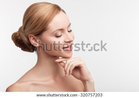 Cute young healthy girl is standing and relaxing. Her shoulders are naked and eyes are closed. She is touching her face gently and smiling. Isolated and copy space in right side - stock photo