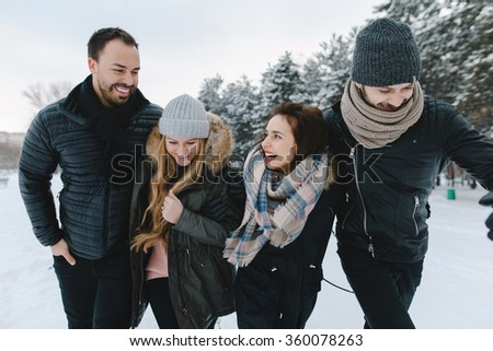 Cute young hipster couples walking in the snow having fun in winter park on a bright day hugging each other and smiling  - stock photo