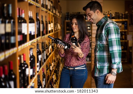 Cute young Hispanic couple trying to decide which bottle of wine to buy among so many options - stock photo