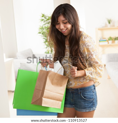 Cute young Latina woman holding shopping bags wearing yellow shirt with flowers and jean shorts. - stock photo