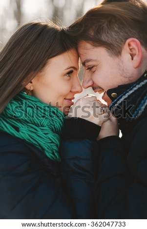 Cute young man and pregnant young woman having fun in winter park on a bright day hugging each other and smiling - stock photo
