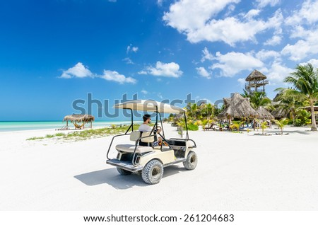 Cute young man driving golf cart along tropical white sandy beach during her Caribbean vacation on Holbox island, Mexico - stock photo
