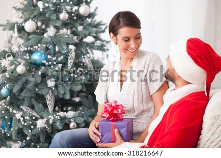 Cute young man in costume of Santa Claus is sitting in chair near Christmas tree. He is holding the woman on knees and giving her a present. The husband and wife are smiling - stock photo