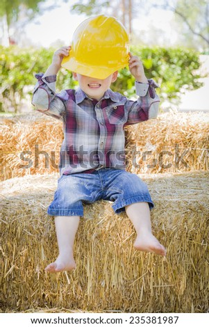 Cute Young Mixed Race Boy Laughing with Hard Hat Outside Sitting on Hay Bale. - stock photo