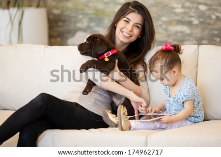 Cute young mom spending time with her daughter and a puppy - stock photo