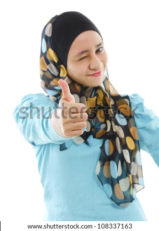 Cute young Muslim girl giving a thumb up sign over white background, focus on thumb. - stock photo