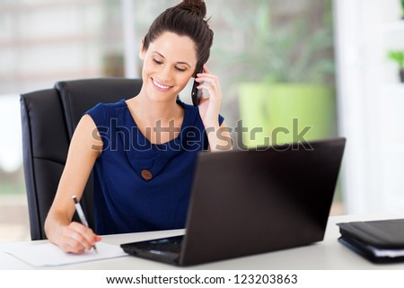 cute young office worker talking on cell phone in office - stock photo