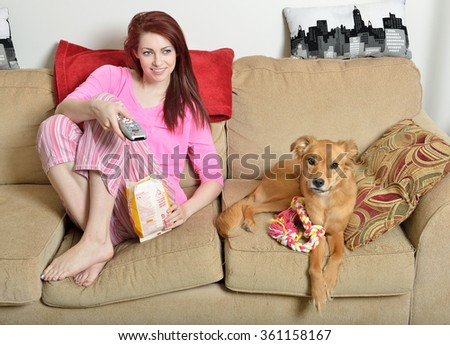 Cute young red-haired woman in pink pajamas sitting in living room eating popcorn with her adorable dog next to her on couch - stock photo