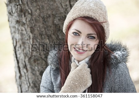 Cute young red-haired woman in winter coat, knit hat, and scarf smiling as she stands outside next to tree with light snow on it.  - stock photo
