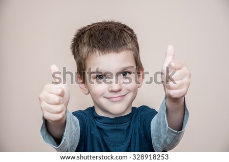 Cute young smiling boy with thumbs up - stock photo