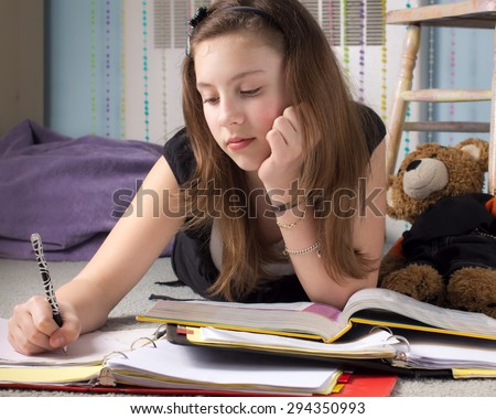 Cute young teenage girl surrounded by books doing homework in her bedroom. - stock photo