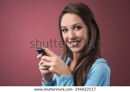 Cute young teenager girl texting with smartphone and smiling at camera - stock photo