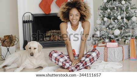 Cute young woman and her dog at Christmas sitting together on the floor in front of the decorated tree with gifts smiling happily at the camera. - stock photo