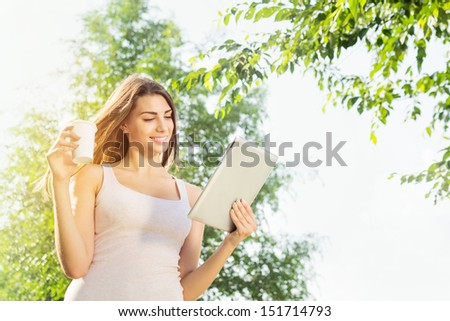 Cute young woman drinking coffee using tablet computer outdoors - stock photo