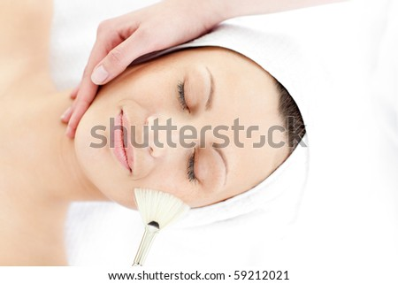 Cute young woman enjoying a beauty treatment in a spa center - stock photo