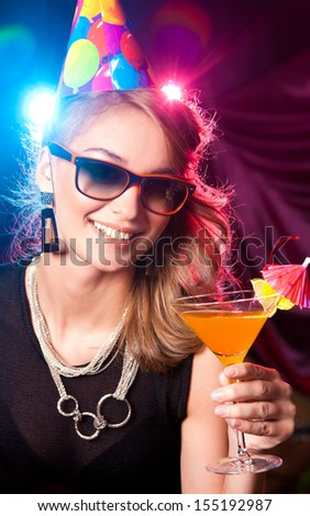 Cute young woman having cocktails at a night club - stock photo