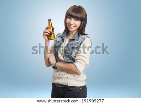 Cute young woman holding a bottle of beer - stock photo