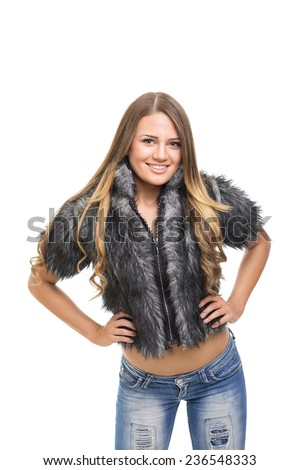 Cute young woman in gray fuzzy jacket. Closeup studio portrait of beautiful blonde Caucasian teenage girl with fuzzy gray coat and jeans smiling isolated on white background. - stock photo