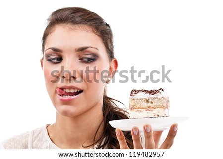 Cute young woman licking her lips with a delicious piece of cake - stock photo