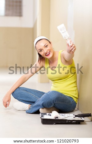 cute young woman painting new home wall - stock photo