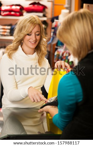 Cute young woman paying after successful purchase with credit card - girl in shopping - stock photo