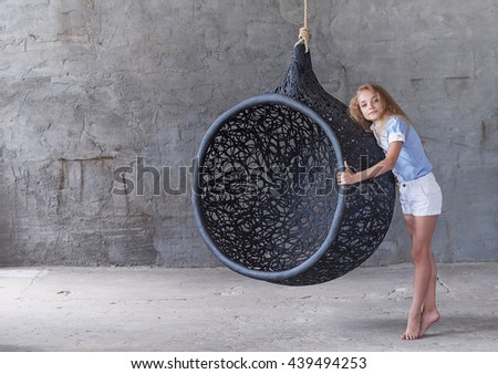 Cute young woman posing near big oval black artistic chair over grey background. - stock photo