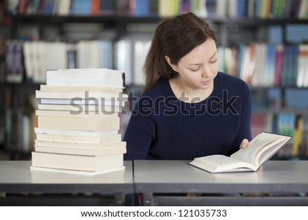 Cute young woman reading at the library - stock photo