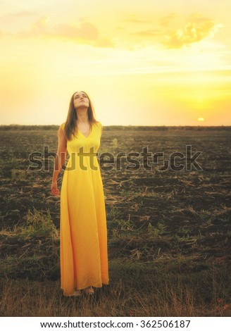 Cute young woman relaxed breathing fresh air, standing  with closed eyes against sunset field. - stock photo
