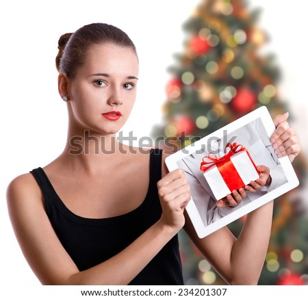 Cute young woman showing tablet computer touch pad gadget with the gift box on a screen. Christmas concept. - stock photo