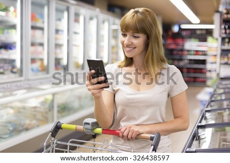 Cute young woman texting on her cell phone in supermarket. - stock photo
