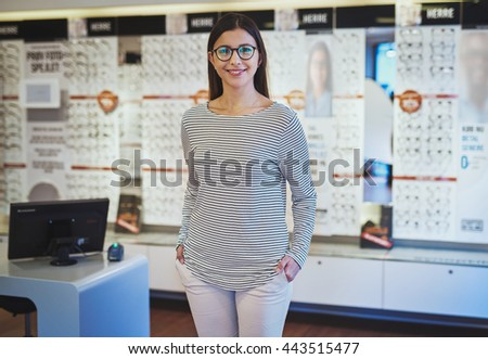 Cute young woman wearing prescription eyeglasses and striped shirt with hands in pockets next to register and display in store - stock photo