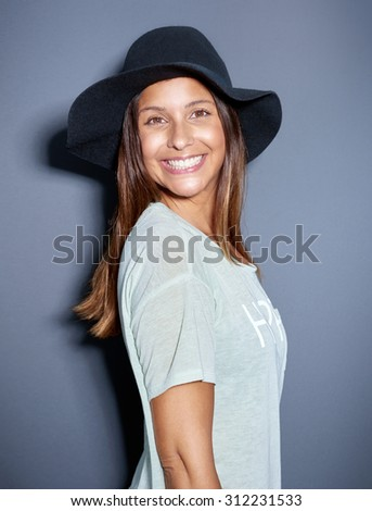 Cute young woman with a big beaming smile wearing a trendy felt hat standing grinning at the camera over grey in a fun humorous portrait - stock photo