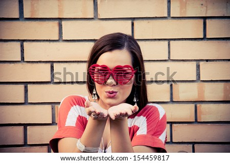 Cute young woman with heart-shape eyeglasses sending kiss, with yellow brick wall in the background - stock photo