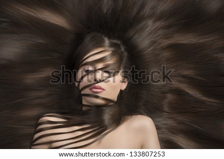cute young woman  with long  dark hair laying down and some locks on the face and the neck - stock photo