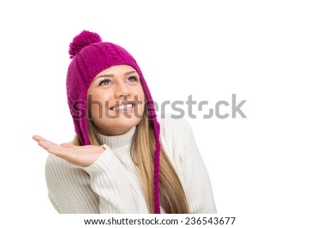 Cute young woman with pink beanie hat looking up. Beautiful blonde Caucasian teenage girl smiling looking up isolated on white background. Winter fashion. - stock photo