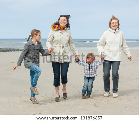 Cute young woman with two kids and grandmother having fun on the Dutch beach - stock photo