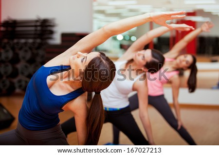 Cute young women practicing the extended side angle yoga pose during a class - stock photo