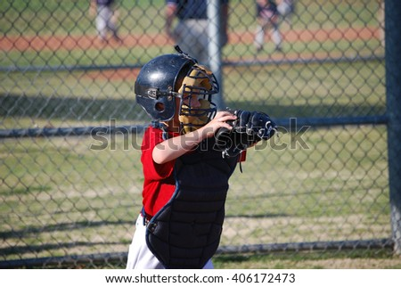 Cute youth baseball boy catching during a game. - stock photo