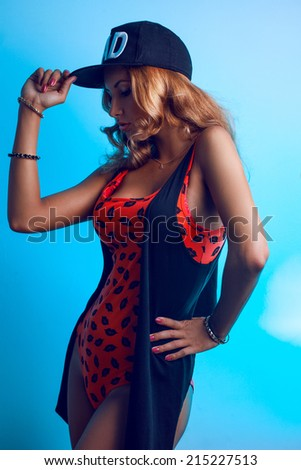 Cutie adult girl in red swimming suit and black hat on blue background in studio - stock photo