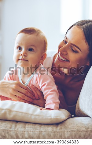 Cutie with her beautiful mommy. Cheerful young woman hugging her baby girl and looking at her while sitting on the couch at home - stock photo