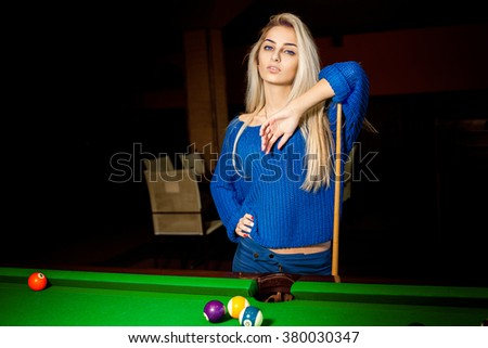 Cutie young blonde with blue eyes plays pool billiard. Billiard sport concept. Pool billiard game. American pool billiard. - stock photo