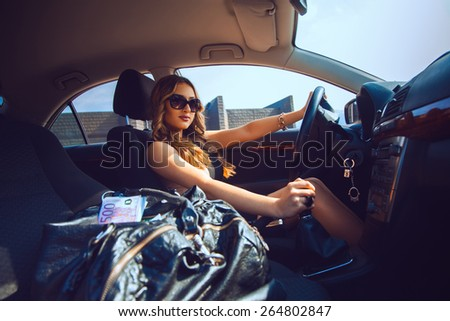 Cutie young girl in sunglasses driving a new car with bag full of money. Inside car photo - stock photo