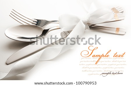 cutlery - knife, spoon and fork tied ribbon. isolated on a white background - stock photo
