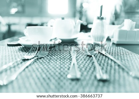 cutlery on the table in a restaurant table setting, knife, fork, spoon, interior - stock photo