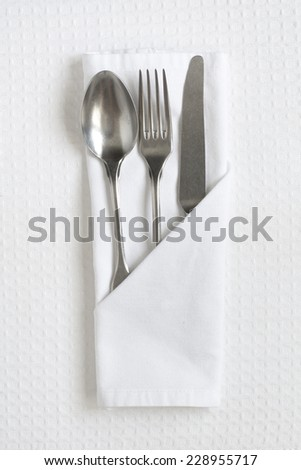 Cutlery on white linen as a table place setting - stock photo